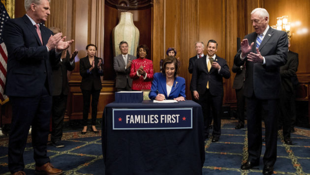 "Nancy Pelosi, wearing a blue suit, sits at a table signing a bill. A sign reading ""families first"" is on the table. A group of officials surrounding her applauds."