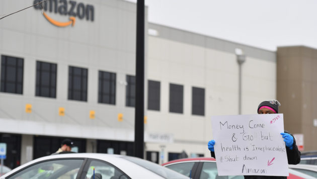 "Outside of an Amazon warehouse, a protester holds a sign saying ""money come and go, but health is irreplaceable. Shut down Amazon."""