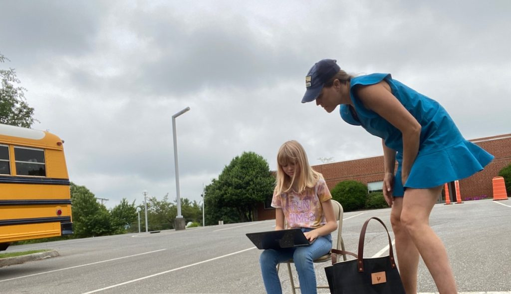 A mother leans over her daughter as the girl types on a laptop next to a school bus in an empty school parking lot.