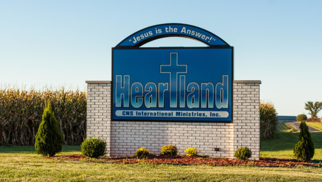 "A blue sign advertises heartland ministries and says ""Jesus is the Answer!"""