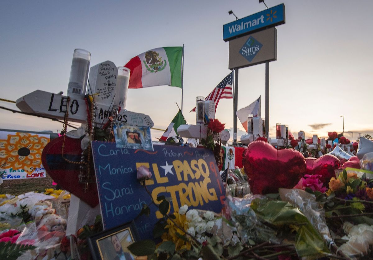 "The sun sets on a memorial left outside an El Paso Walmart. Flowers and balloons crowd around a sign that says ""El Paso Strong."" A Mexican flag and US flag fly behind the memorial."