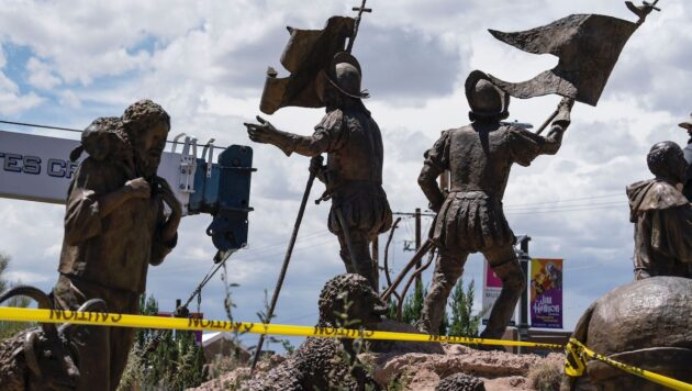 Statues of Spanish conquistadors are surrounded by a perimeter of caution tape. The arm of a heavy crane stands in the background.