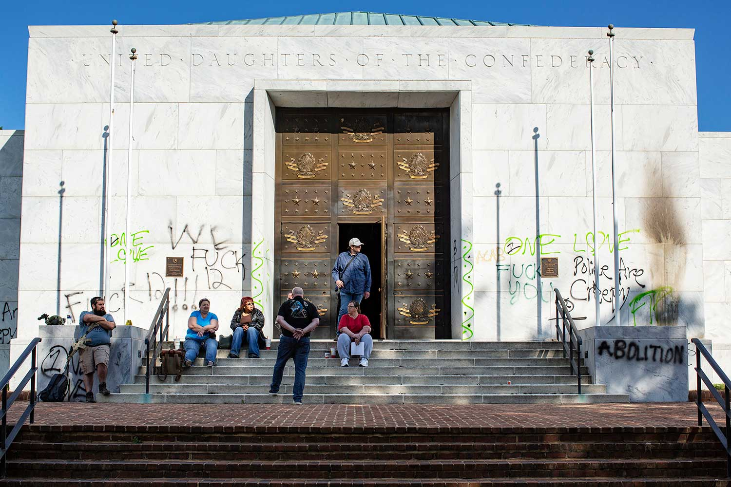 People sit and stand on the steps of the United Daughters of the Confederacy headquarters. The building is tagged with anti-police graffiti.
