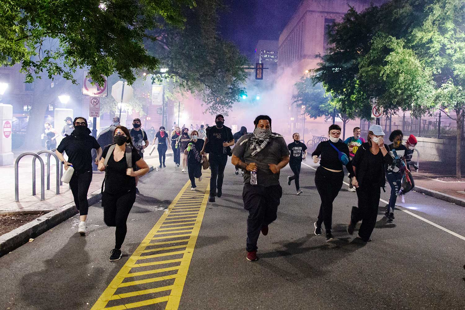 Protesters wearing protective face masks run down a street. The air is hazy with tear gas.