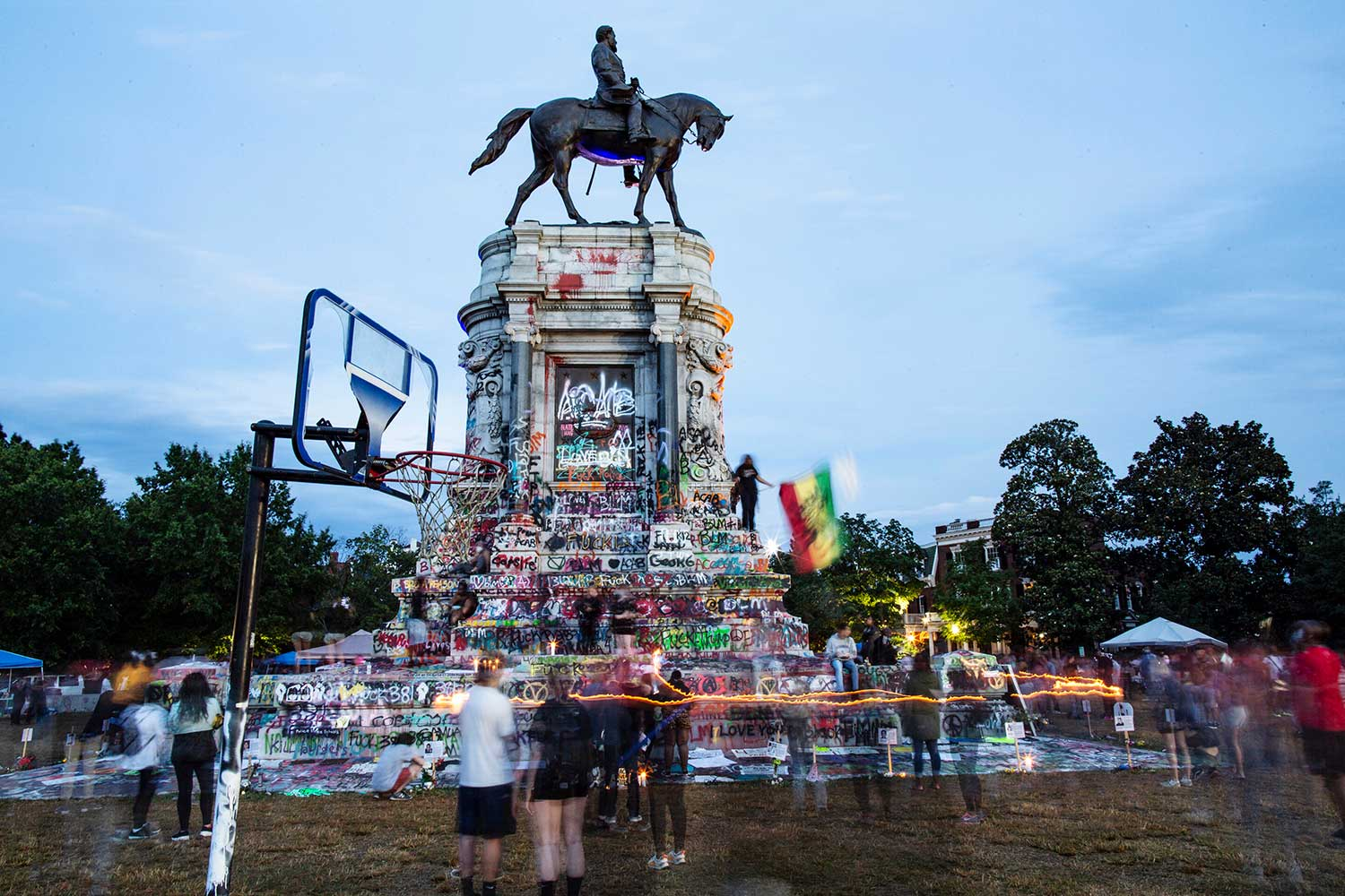 People gather around Richmond's Robert E. Lee statue, which is covered in colorful graffiti.