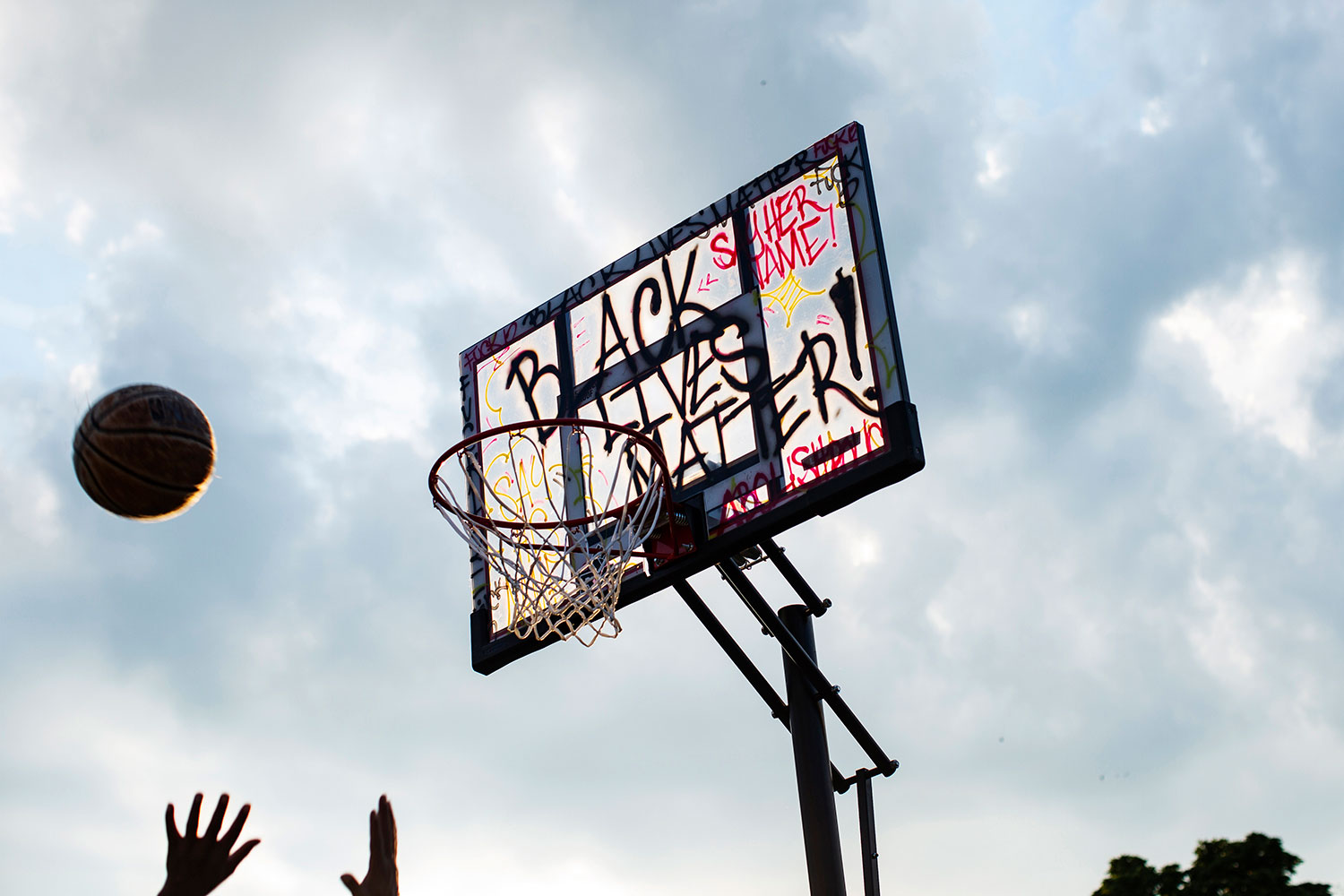 "A large portable basketball hoop, tagged with ""Black Lives Matter"" and other graffiti, is silhouetted against the sky."