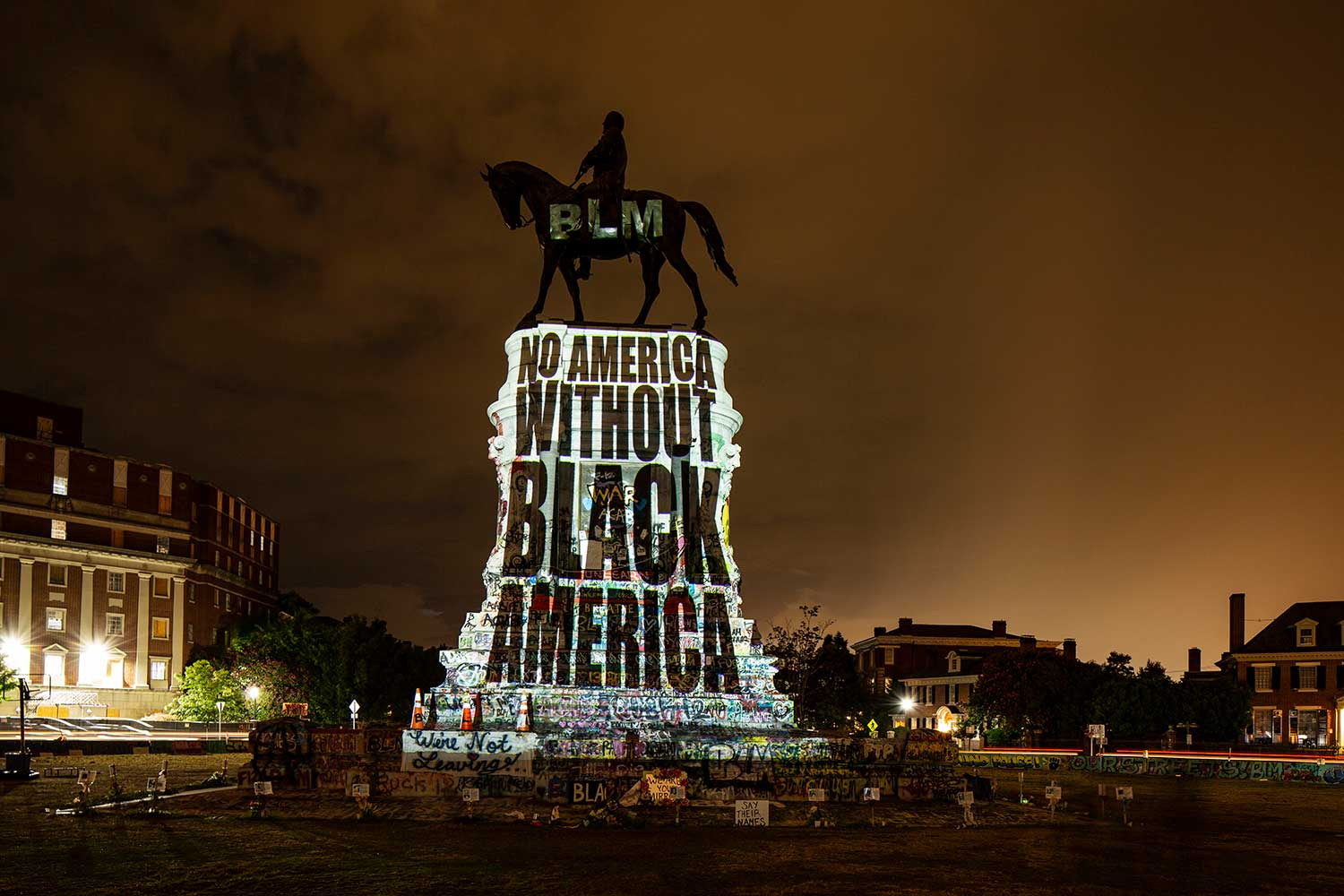 The Robert E. Lee statue at night, with a light installation projecting this message onto it: BLM. No America Without Black America.
