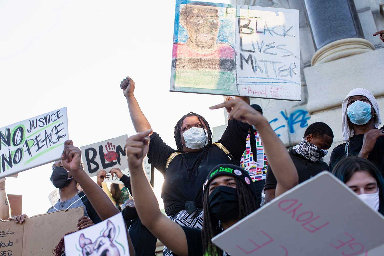 Protesters wearing protective face masks raise their fists and carry hand-drawn Black Lives Matter signs.