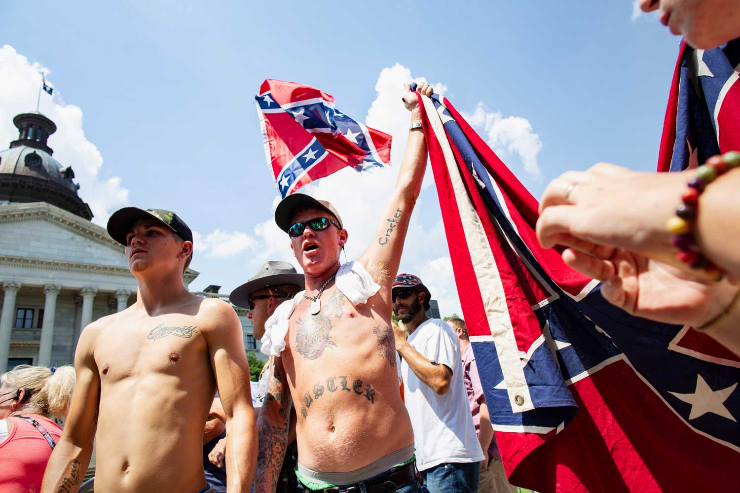 Shirtless tattooed White men carrying Confederate flags are among a group gathered in front of the South Carolina State House.