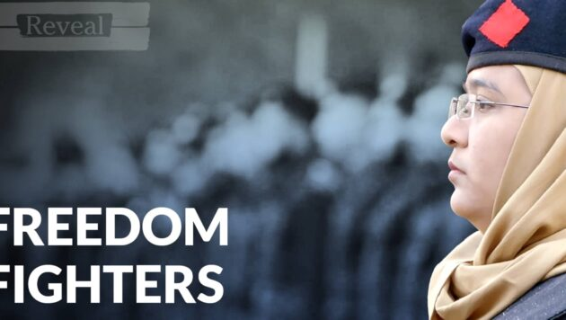 A still from the video Freedom Fighters shows a woman in a tan headscarf and blue beret staring off into the distance.