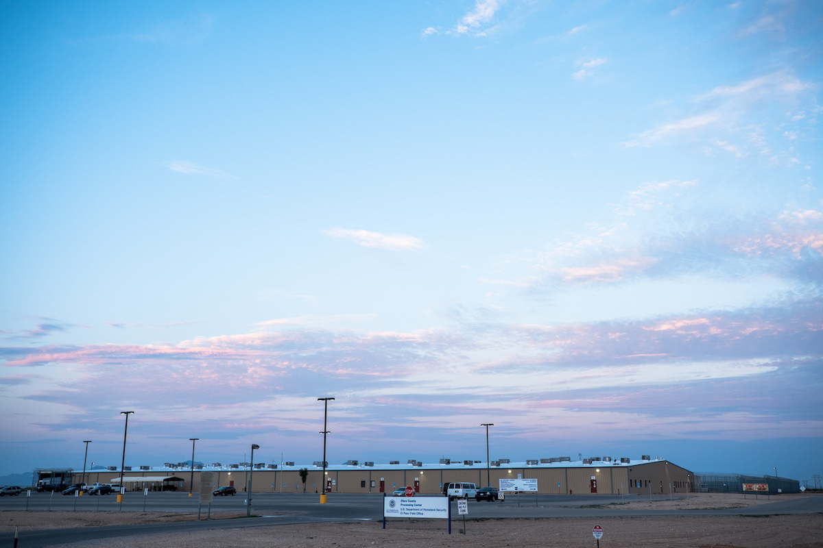 A single-story detention facility for immigrants is covered with khaki-colored corrugated siding.