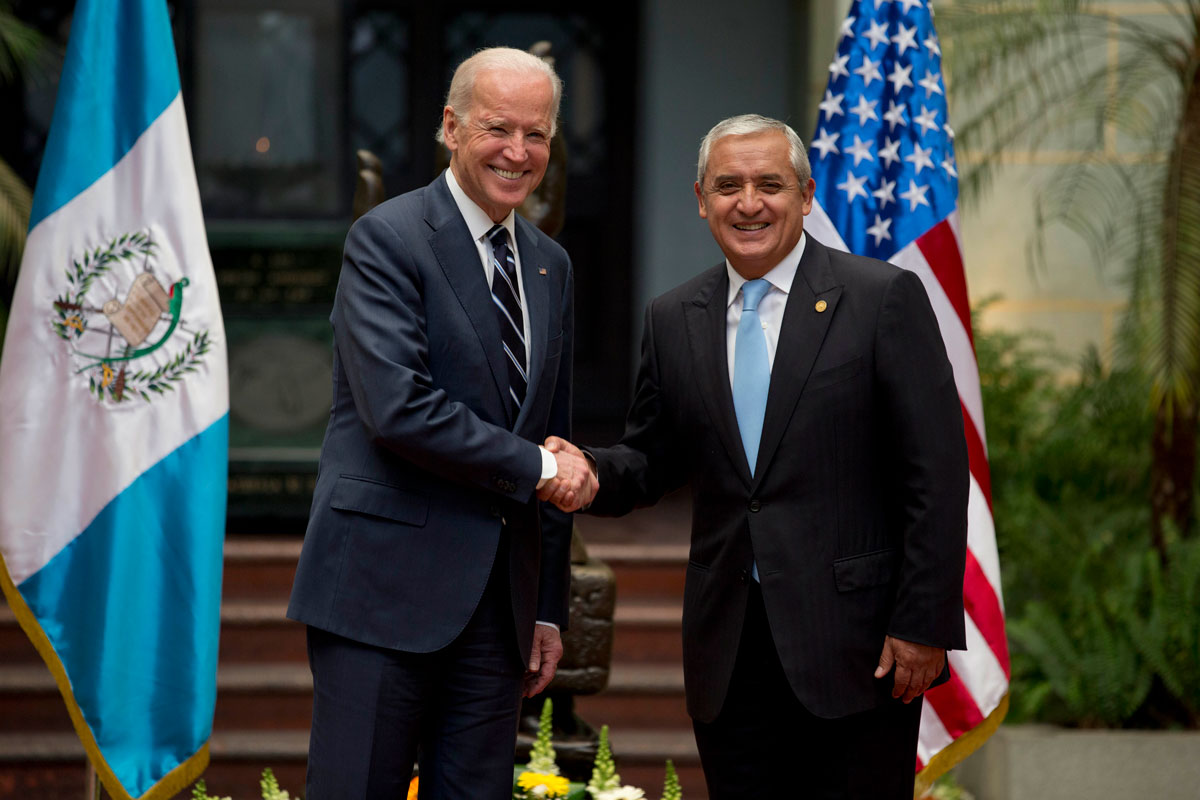 U.S. Vice President Joe Biden shakes hands with Guatemalan President Otto Pérez Molina during an official event. Guatemalan and American flags stand in the background.