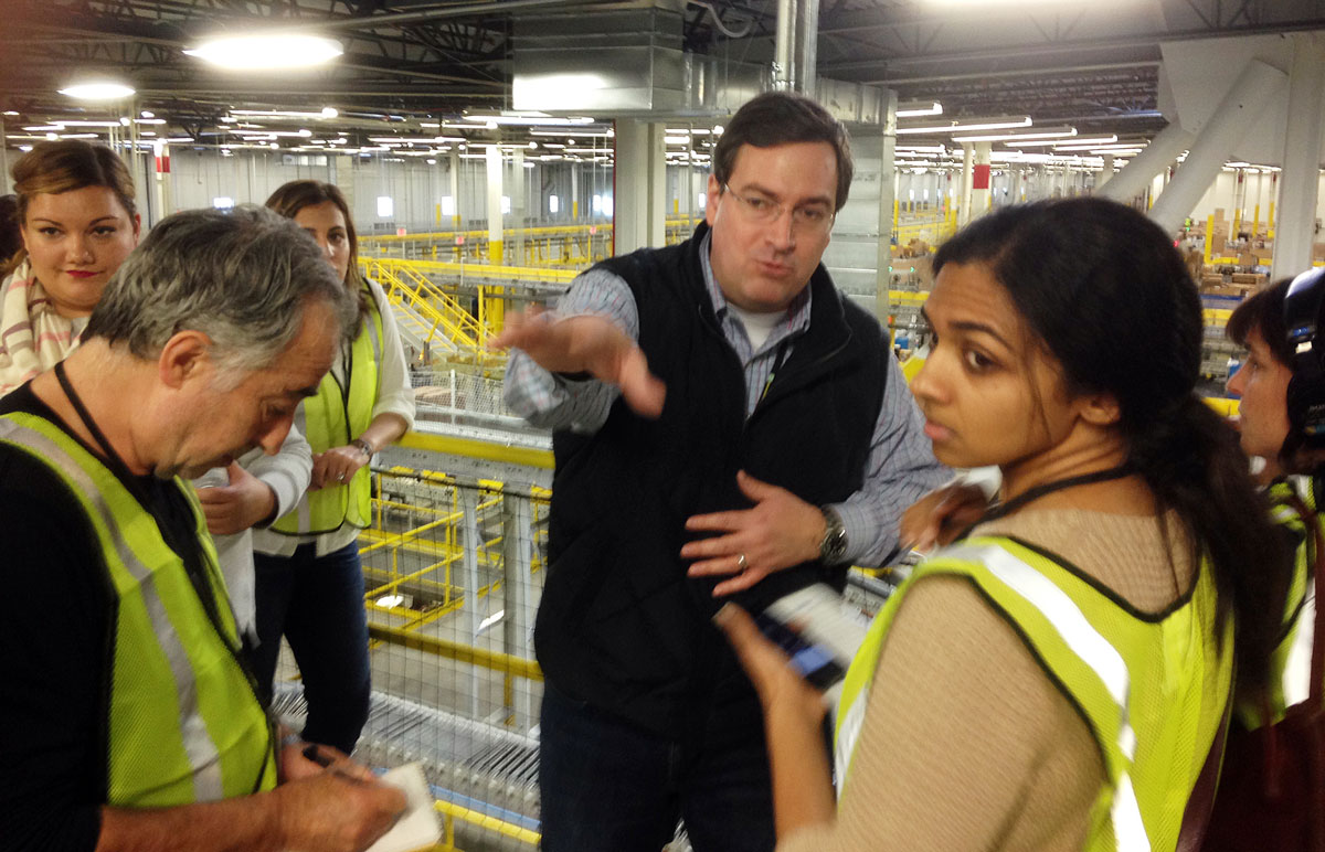 Dave Clark takes visitors on a tour of an Amazon fulfillment center. The visitors wear safety vests.