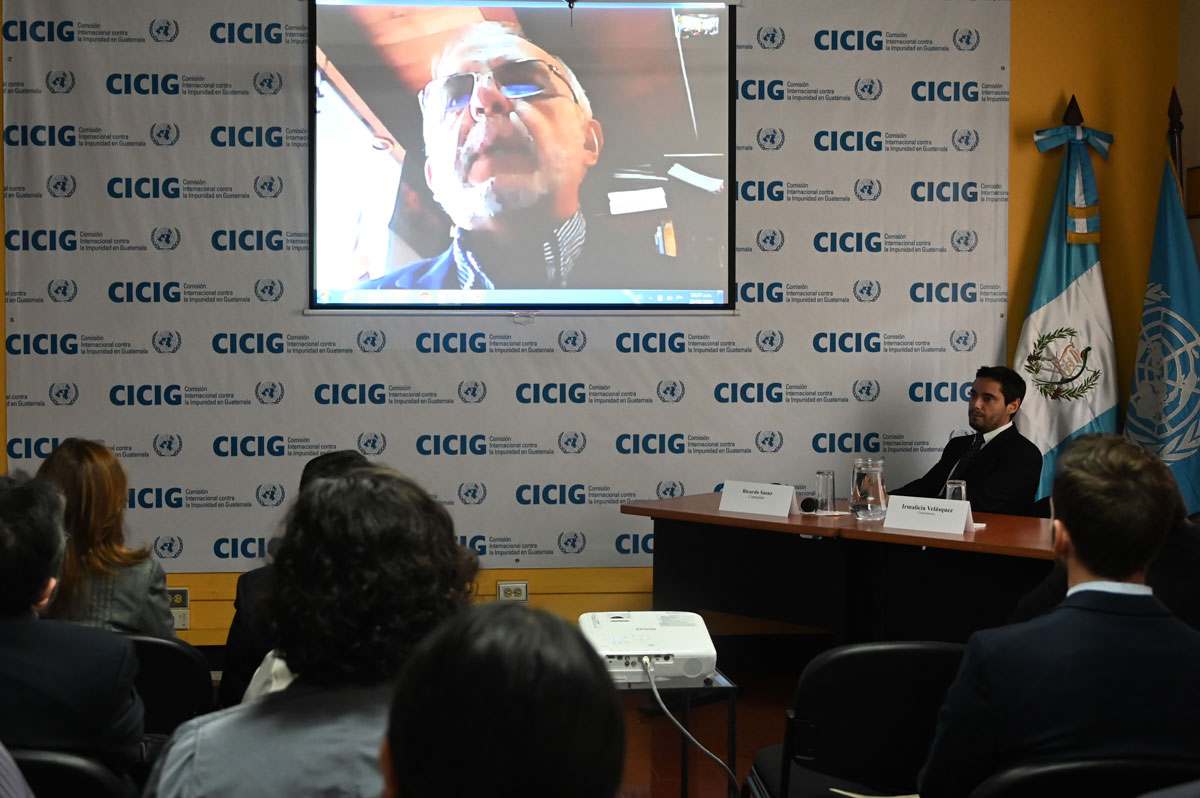 An audience watches a video stream of Iván Velásquez that is projected on a screen. The screen hangs in front of a CICIG backdrop.