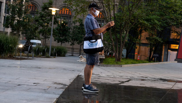 A man wearing a face mask carries a messenger bag with the Census Bureau's logo.