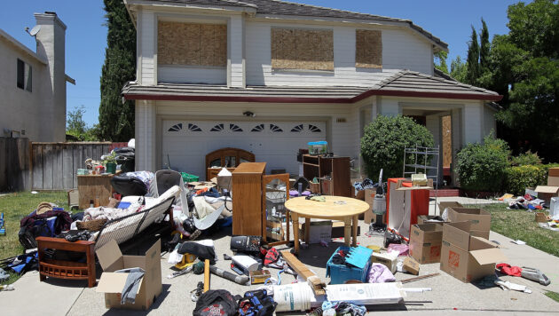 Furniture and personal items are haphazardly strewn in front of a house. The home's windows are boarded up.