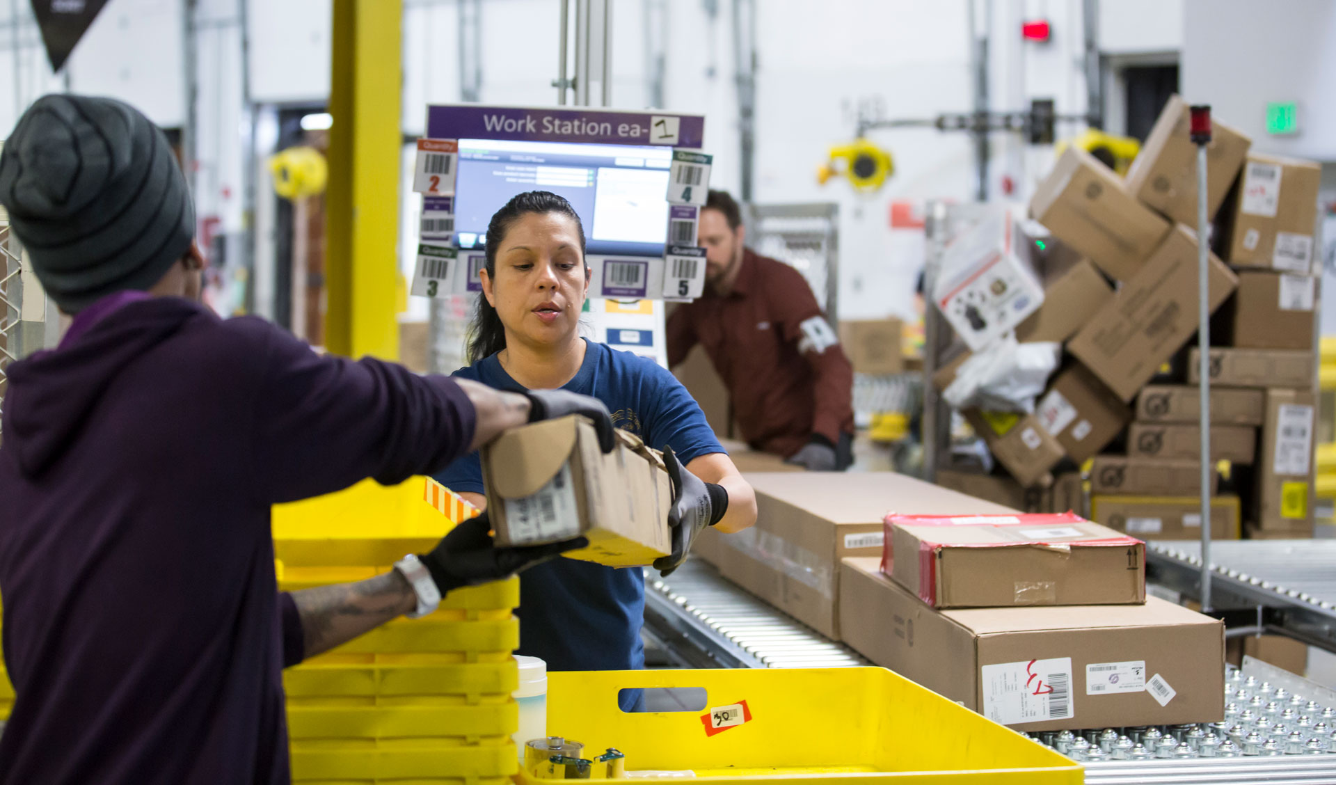 One worker hands a box to another worker as they stand in front of a conveyor belt filled with cardboard boxes.