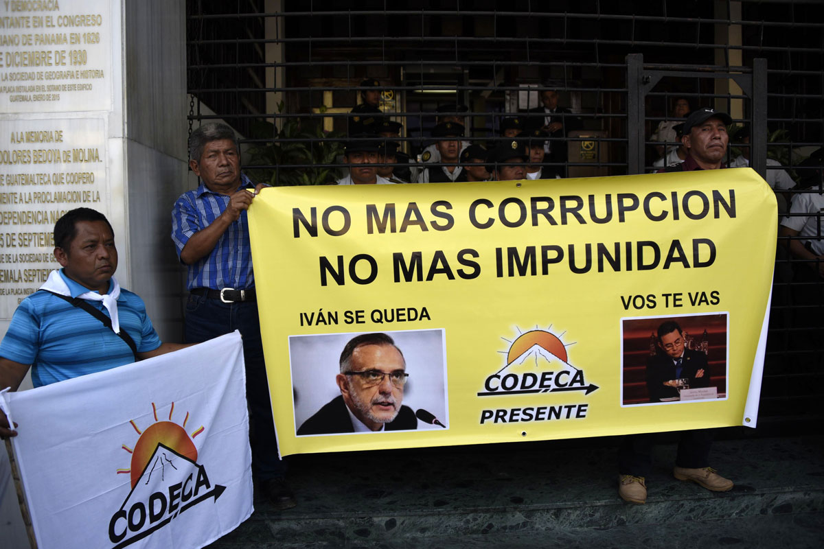 "Several men hold a banner, which features photos of Iván Velásquez and Jimmy Morales. The banner's top says: ""No mas corrupcion, no mas impunidad."""