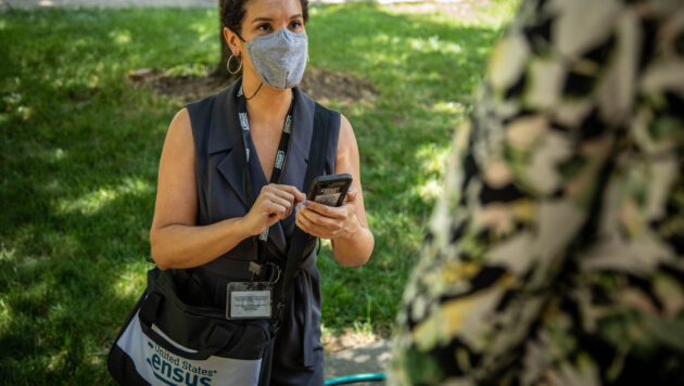 A census worker wearing a facemask and carrying a phone and branded bag talks to a person in the foreground.
