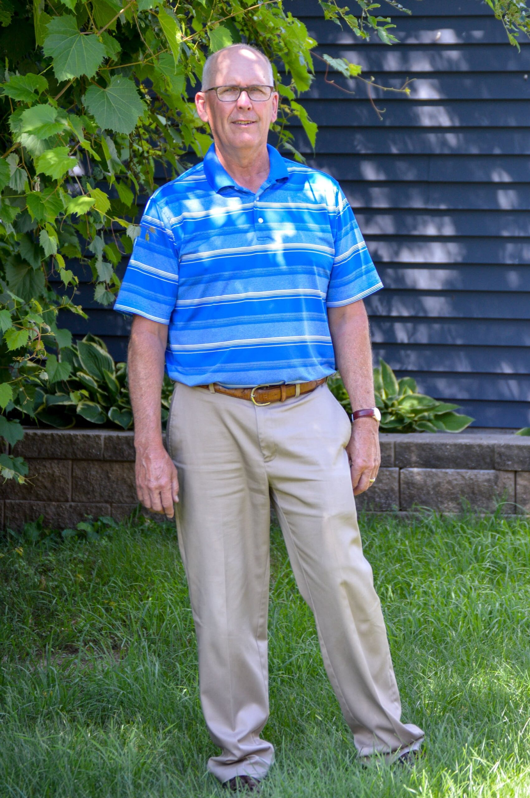 A standing portrait shot of Bob Capen wearing a blue polo and khaki trousers.