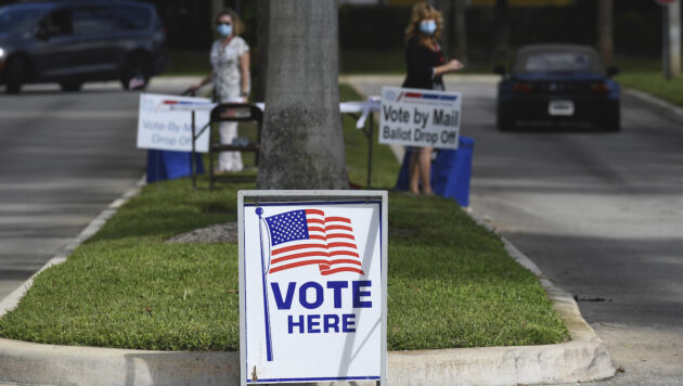 """Two people stand near signs that read, """"Vote by Mail Ballot Drop Off."""""""