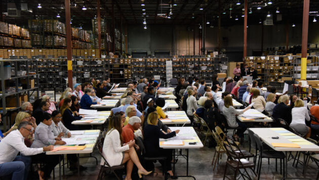 Dozens of people sit side by side at folding tables, reviewing paper ballots. They are in a large warehouse surrounded by shelves filled with boxes.