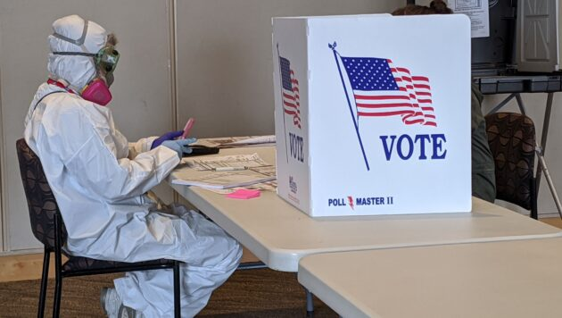 An elections worker wears a hazmat suit as they sit next to a sign saying VOTE.