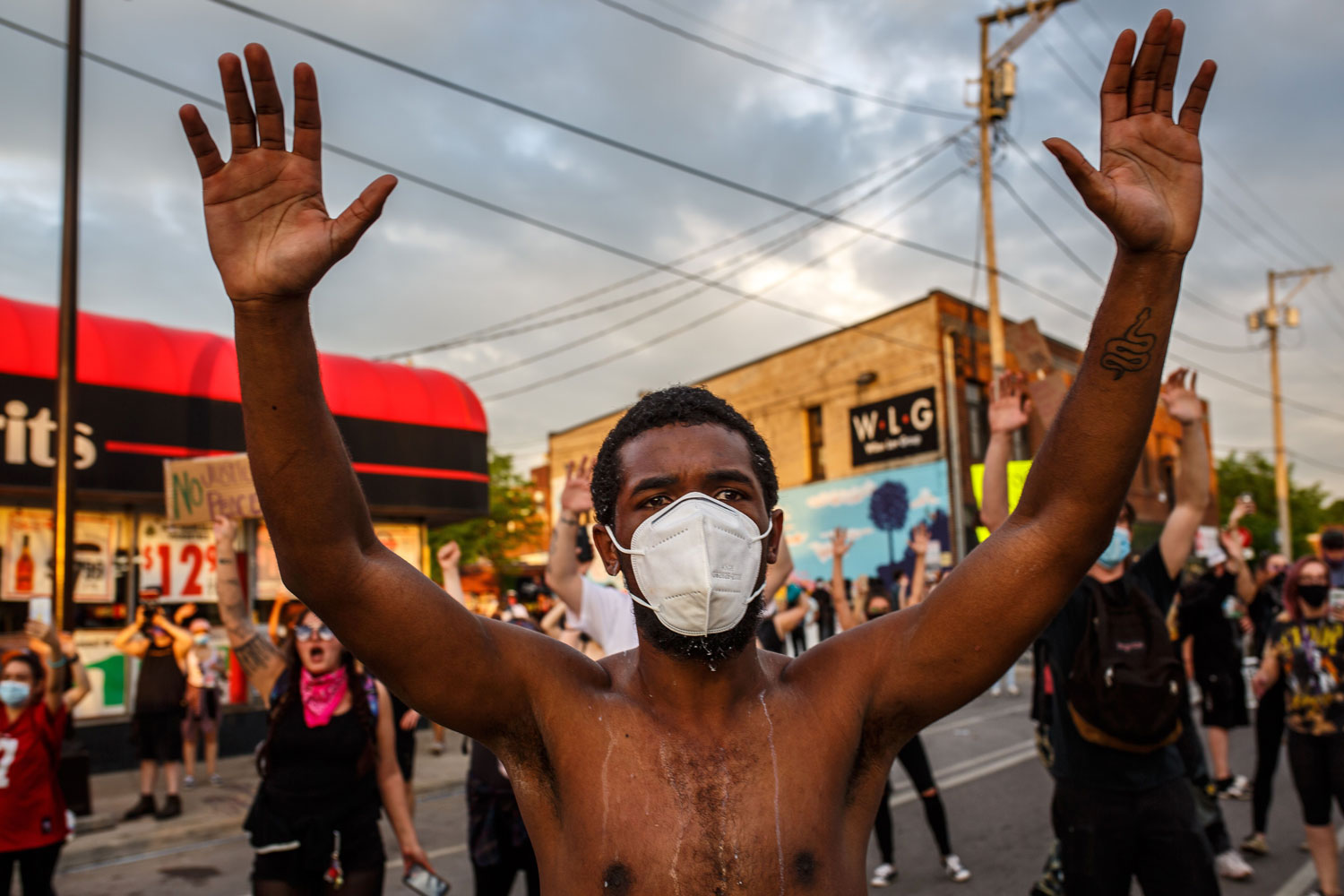 In the foreground, a shirtless man wearing a disposable face mask stands in a street, holding his hands in the air. Dozens of protesters behind him do the same.