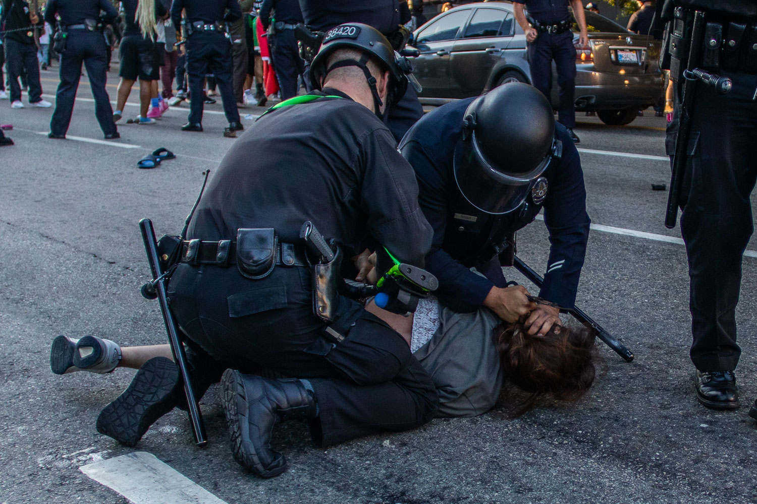 Two police officers, both wearing helmets, pin a protester down in the middle of a street.