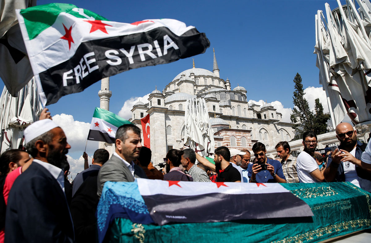 "A group of people gather outside a mosque. Several ""Free Syria"" flags wave among them."