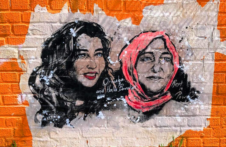 A mural on an orange wall depicts portraits of journalist Halla Bakarat and her mom.